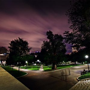 A photograph Boston Common at night, the sky has an eerie purple tone, the common looks haunted...