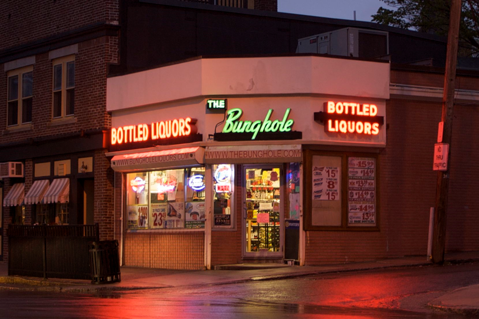 Illuminated by red neon, the store front of bunghole Liquors hides what used to be a Speakeasy, with alcohol smuggling tunnels underneath