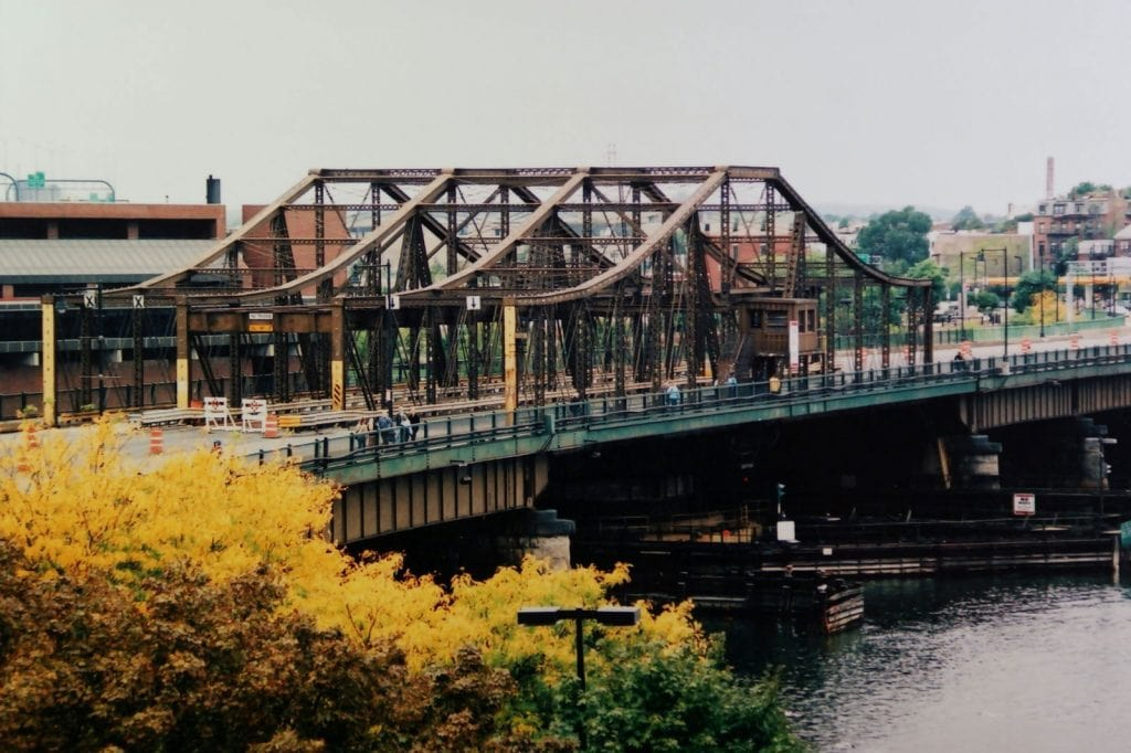 A photograph of a three lane steel frame bridge crossing a wide river, in Boston, Massachusetts, the bridge is haunted by the ghost of Paul Rugg