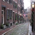 image shows brick street with large brick row homes in Boston.