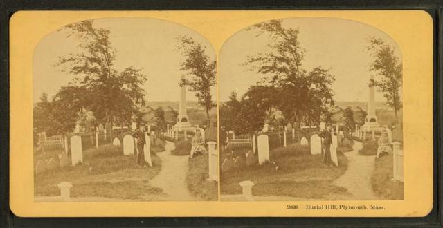 photo shows a very old photograph of a man standing next to a grave marker in burial hill