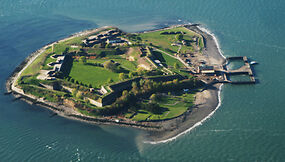 photo shows George's Island from an aerial view, surrounded by ocean. Fort Warren is also pictured on the bottom left of the island, with large concrete walls and grassy fields within.