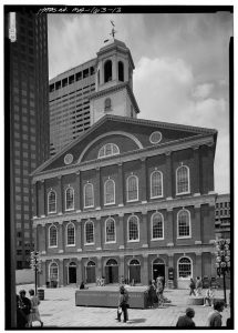 Photo is made to look antique, it shows the façade of the man building in Faneuil Hall with people walking about its front doors.